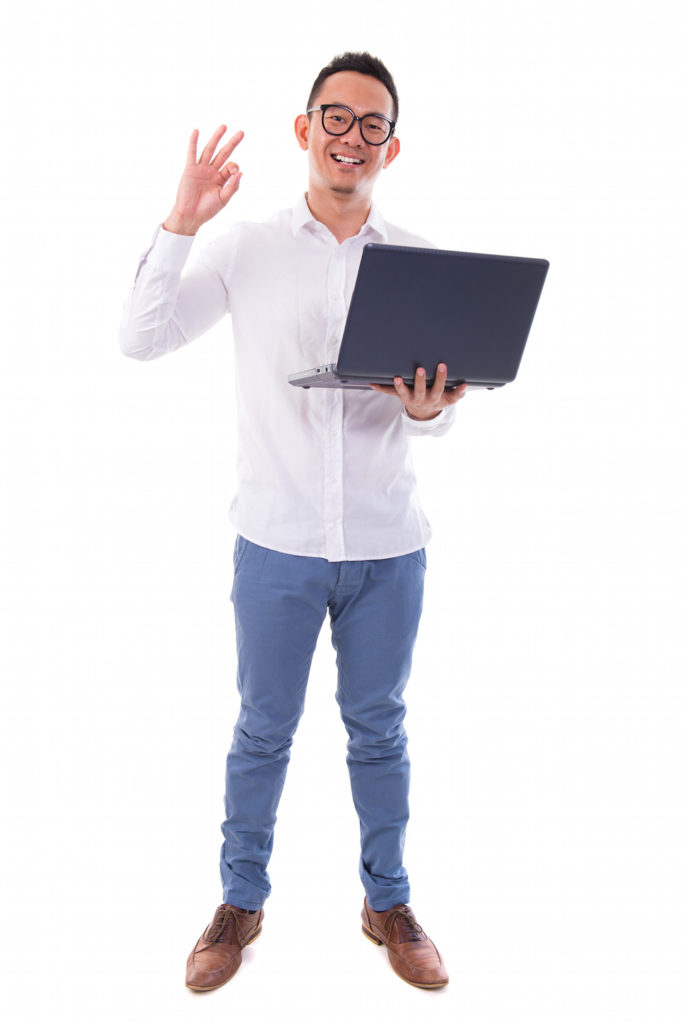Full length of happy Asian businessman using laptop showing okay hand sign standing isolated over  white background